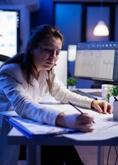 책상에 앉아 있는 새 건물 프로젝트를 위한 청사진을 분석하고 일치시키는 여성 건축가