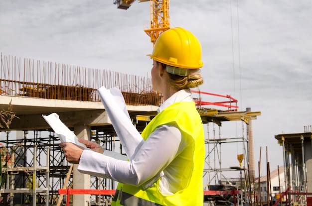 Woman architect at construction site with plans in hands looking at new building