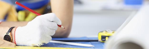 青写真のクローズアップに鉛筆で描く手袋の女性建築家
