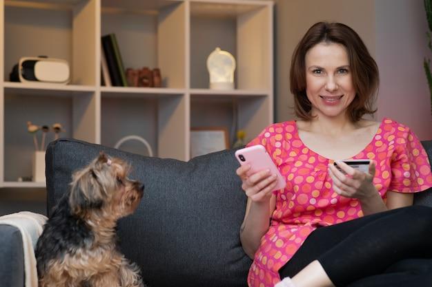女性は、リビングルームのソファーに座っている間、クレジットカードでオンラインで購入しています。女性はスマートフォンを使用してオンライン取引を行っています。