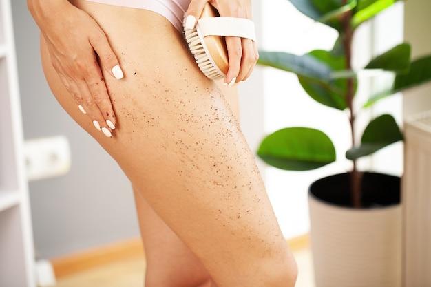 여자 팔은 마른 솔을 다리 꼭대기에 들고 셀룰 라이트 치료와 드라이 브러싱을합니다.