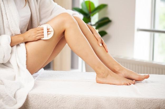 彼女の足の上部に乾いたブラシを保持している女性の腕、セルライト治療と乾いたブラッシング。