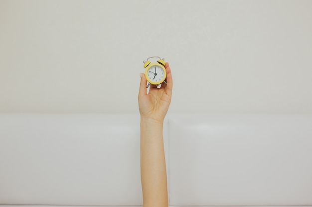 ベッドに横たわっている間、小さな黄色の時計を保持している女性の腕。