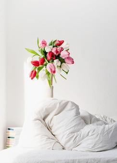 Woman arm outstreched from the blanket holding a bouquet of tulip flowers. woman in bed holding tulip flowers