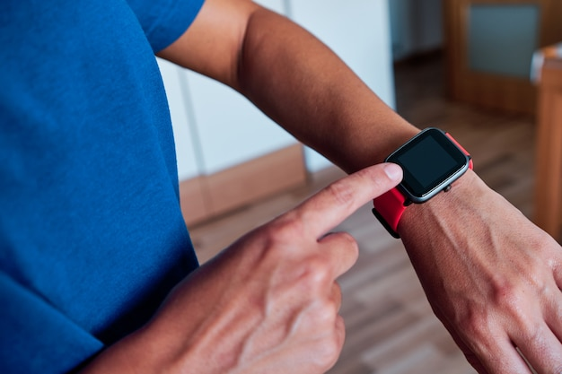 Woman arm using smartwatch to control activity indoor