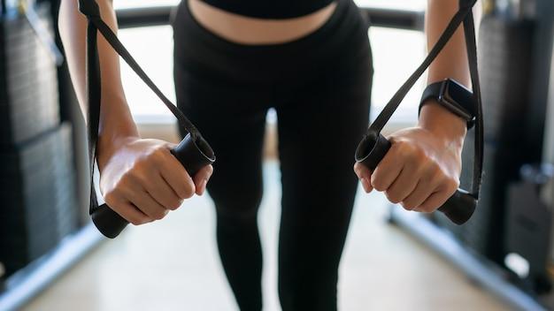 케이블 비행을 하 고 여자 팔 체육관에서 운동.