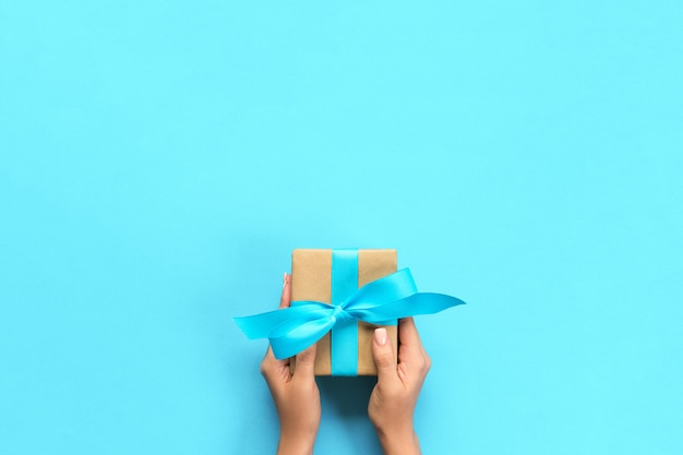 Woman arms holding gift box with blue ribbon on color , top view