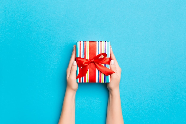 Woman arms holding gift box with colored ribbon on blue table background