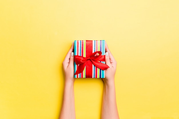 Woman arms holding gift box with colored ribbon on yellow table background