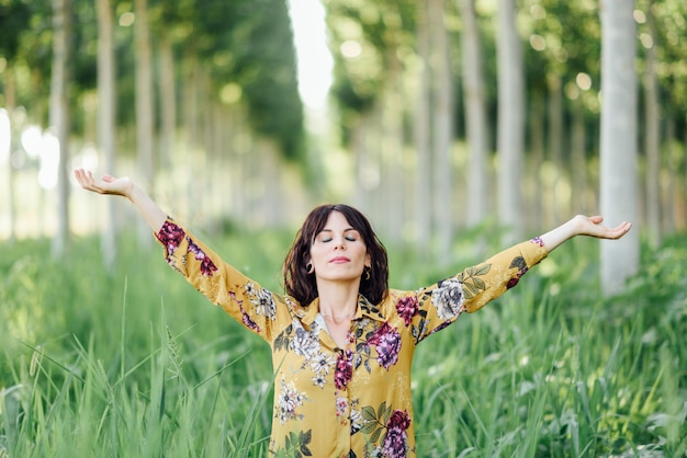 Woman arms raised enjoying the fresh air in green forest.