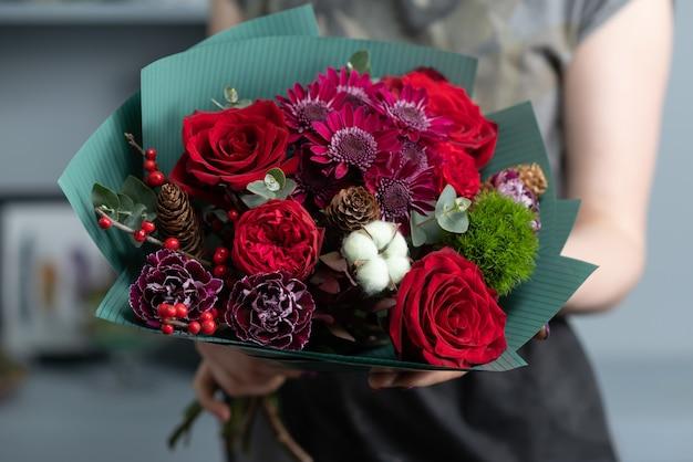 장미, 국화, 카네이션 및 기타 꽃으로 꽃다발을 준비하는 여자