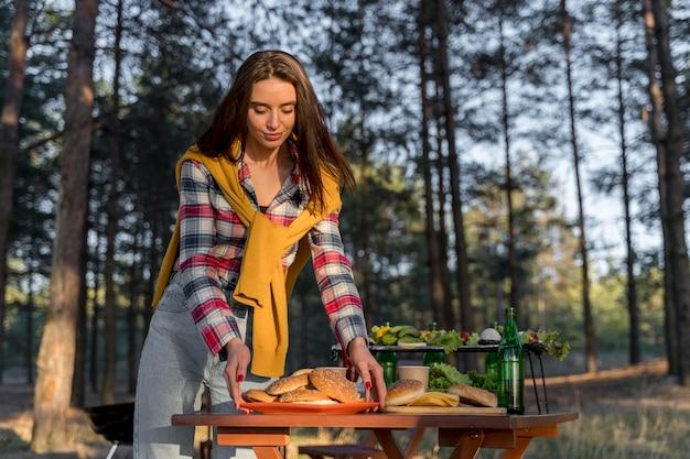 友人がすぐに参加するためにテーブルに食べ物を手配する女性