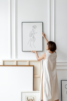 Japandiの装飾部屋の壁にフレームを配置する女性