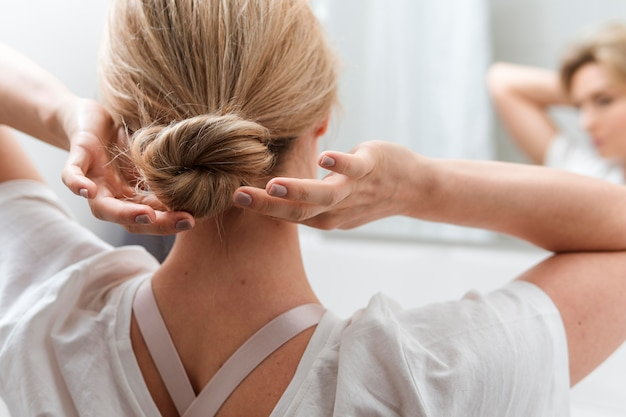 Woman arranging her hair from behind view