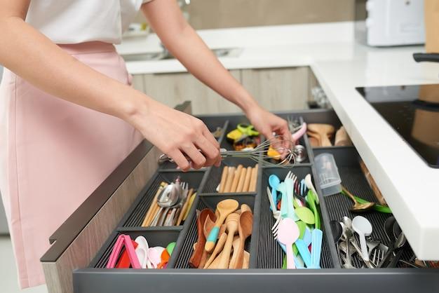 Женщина, устраивающая кухонную утварь.