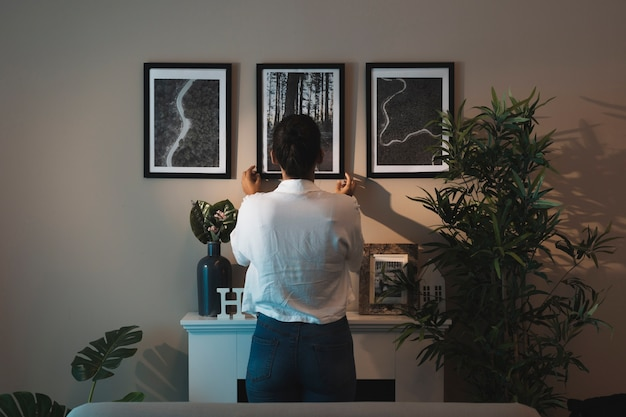 Woman arranging paintings at home