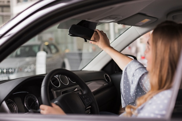 Woman arranging rear-view mirror