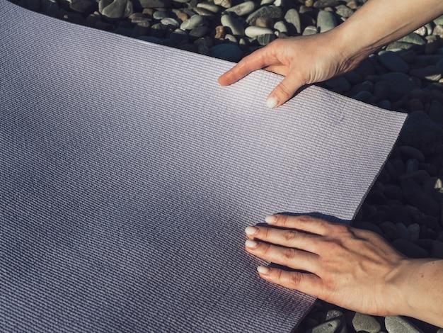 Женщина устраивает коврик для йоги на скалах
