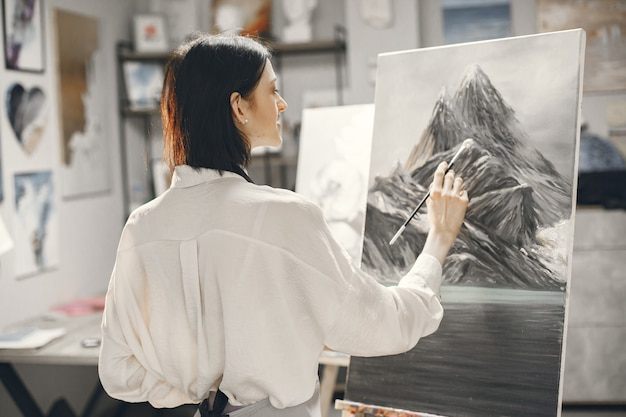 Woman in an art school wearing an apron drawing on an easel.