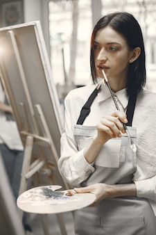 Donna in una scuola d'arte che indossa un grembiule con un gesto pensieroso.