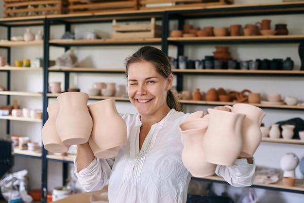 女性職人の陶芸家が手作りの粘土の水差しを手に持っています
