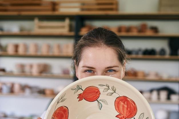粘土製品のクローズアップの後ろから覗く女性職人陶芸家
