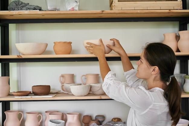 女性職人の陶芸家が手作りの粘土のボウルをラックに置きます