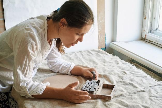 女性職人の陶芸家が粘土に刻印する文字を選択します