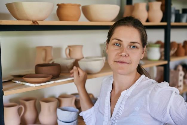 女性職人の陶芸家は、手作りの粘土の道具でラックの背景に立っています