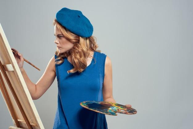 イーゼルアートの創造性の光を描く女性アーティストの青いベレー帽パレット