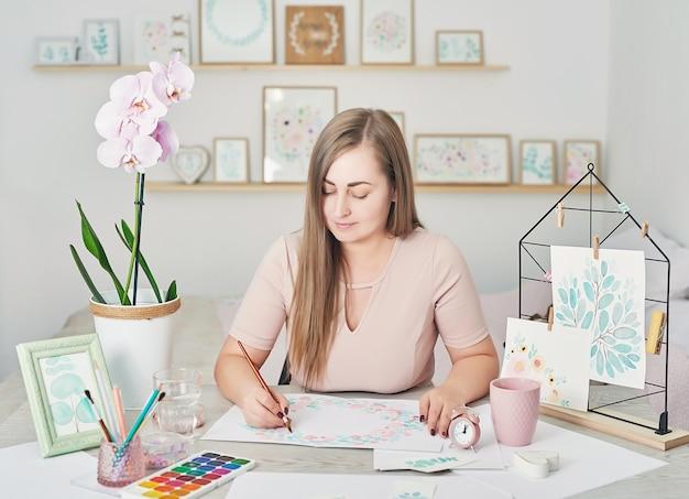 花の水彩画のデザインを描く女性アーティスト