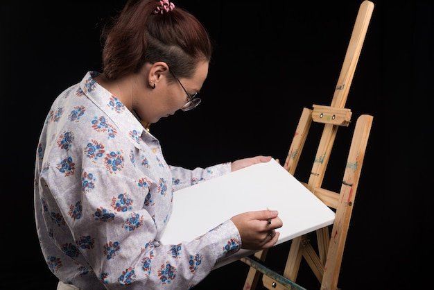黒の背景にブラシで白いキャンバスに何かを描く女性アーティスト。高品質の写真