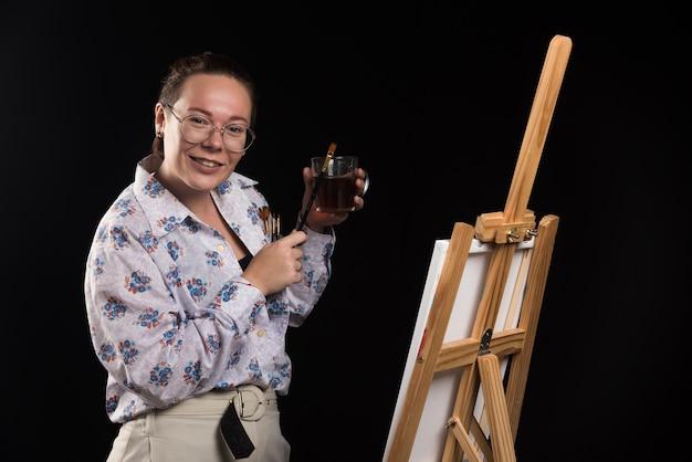 Художник-женщина, держащая кисть и холст на черном фоне.