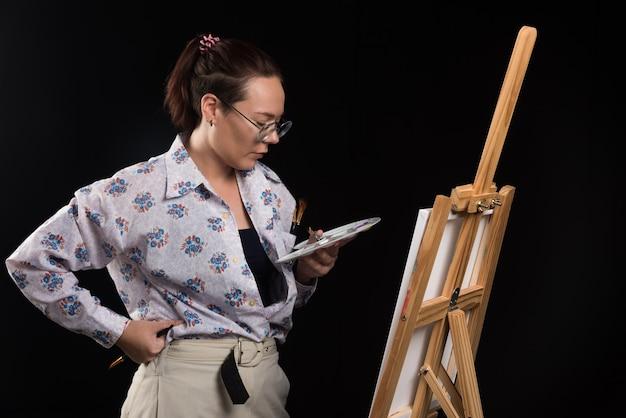 Художник женщина держит кисть и смотрит на холст на черном фоне