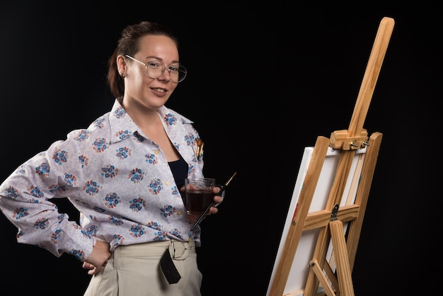 Artista della donna che tiene pennello e tela su sfondo nero. foto di alta qualità