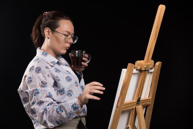 Artista della donna che tiene il pennello e guardando la tela su sfondo nero