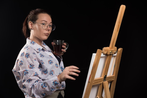 Artista donna che tiene il pennello e guarda la tela su nero