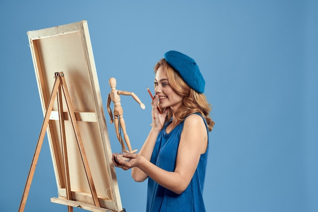 Woman artist holding wooden mannequin easel art in hands creative hobby blue background. high quality photo
