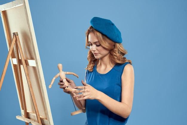 Художник женщина держа деревянное искусство мольберта манекена в руках предпосылка творческого хобби голубая. фото высокого качества