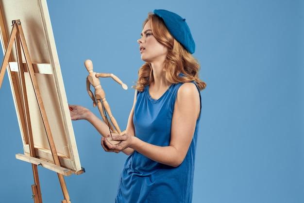 Художник женщина держа деревянное искусство мольберта манекена в руках стена творческого хобби синяя.