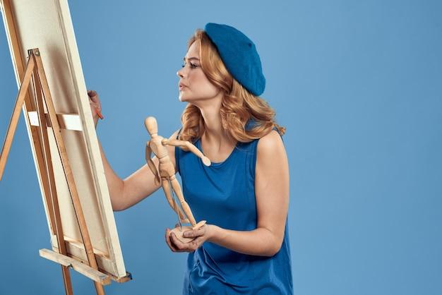 木製のマネキンイーゼルアートを手に持つ女性アーティストクリエイティブホビーブルー。