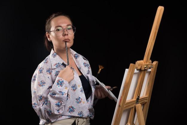 Художник женщина держит кисть во рту и думает на черном фоне. фото высокого качества