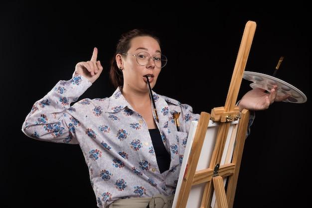 Художник женщина держит кисть во рту и думает на черном фоне.