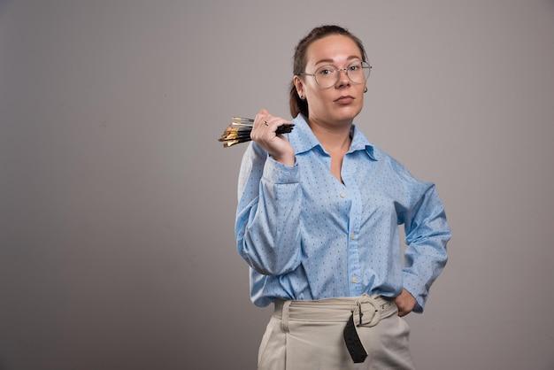 L'artista della donna tiene i pennelli da pittura su gray. foto di alta qualità