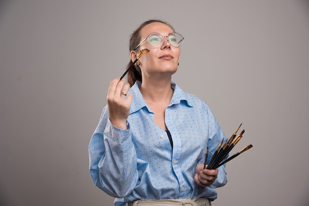 Woman artist holds painting brushes near her face on gray background