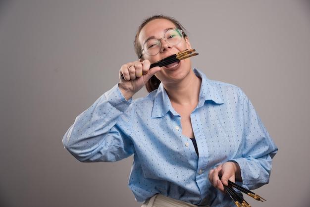 L'artista donna tiene i pennelli da pittura vicino al viso su gray on