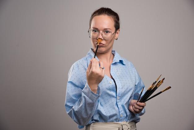 Художник-женщина держит кисти для рисования на сером фоне. фото высокого качества