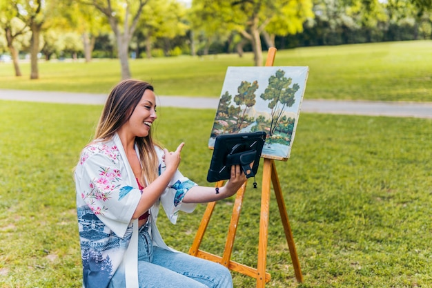 Художница делает видеозвонок, чтобы показать свои работы в парке