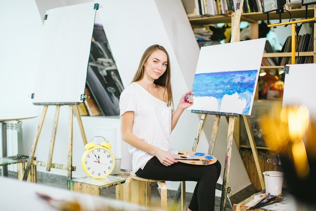 Woman artist painting a picture on easel with oil paints in her workshop
