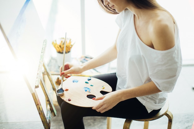 Woman artist painting a picture in a well-lit studio